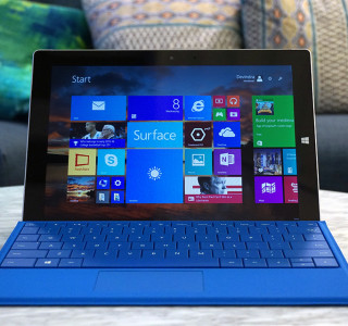 The image shows a surface tablet from the front, with a blue type cover open in front of it. On the screen can be seen Windows 8 tiles