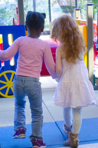 Two little girls walking hand in hand and viewed from behind play at preschool