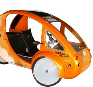 The image shows the Elf, an electric bike. The bike has a chassis around it with no doors, two wheels on the front and one at the rear.