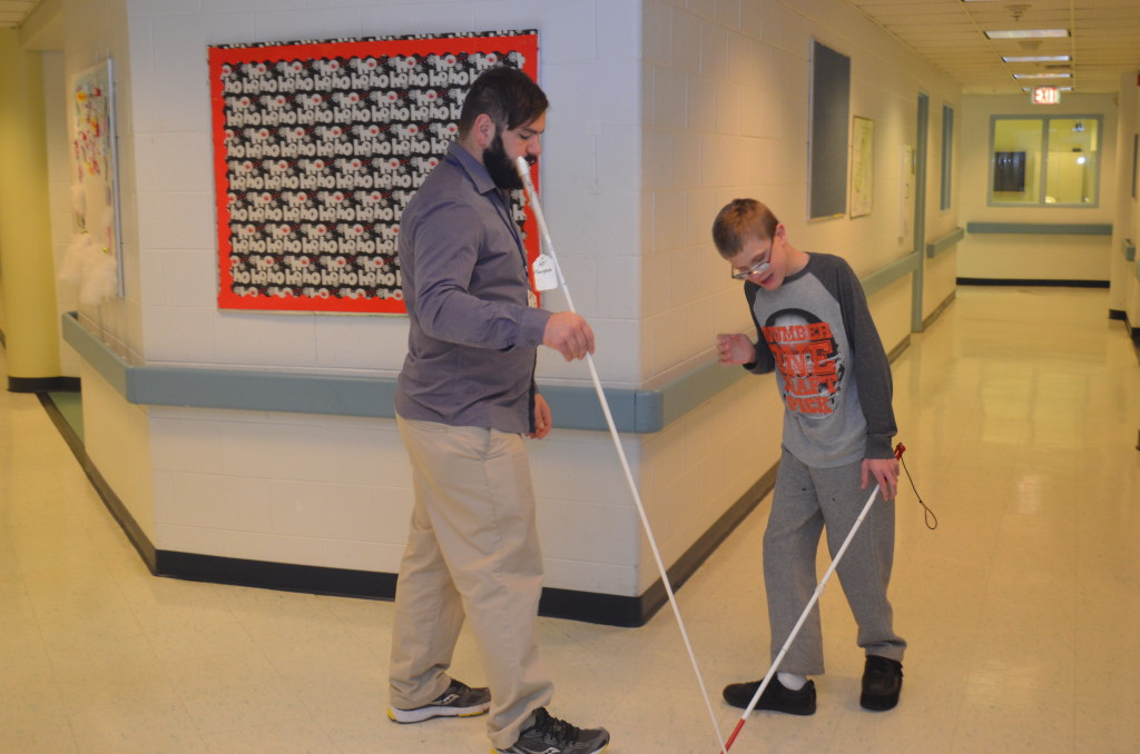A mobility training instructor practices walking with a white cane to a young boy who is blind