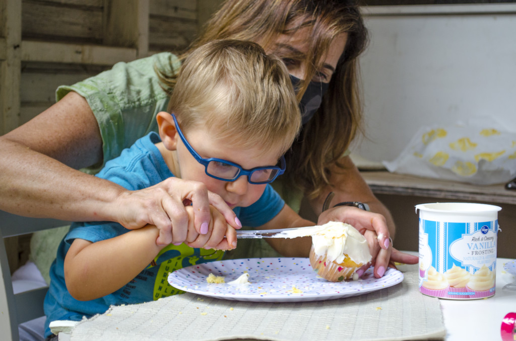 A three year old boy who is visually impaired frosts a cupcake with his vision teacher.