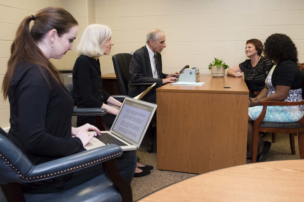 A female client consults with Attorney Paul Rink and his team