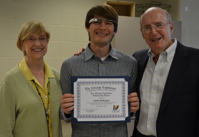 A scholarship recipient displays his certificate with his sponsors