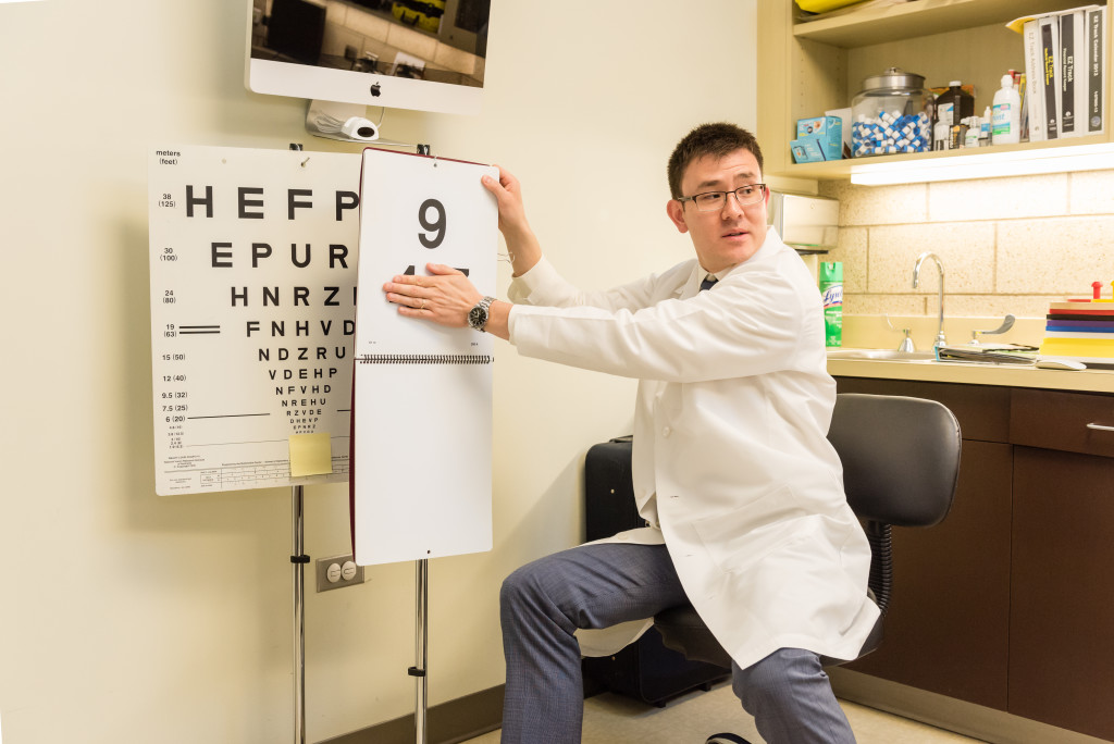 A resident of Optometry flips pages of an eye chart