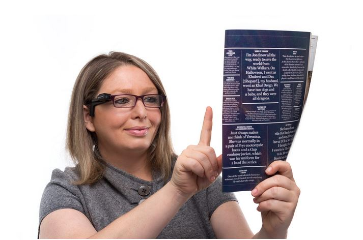 Woman is wearing the OrCam devices and is reading small text on paper