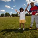 A coach teaching a participant to play beep baseball