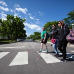 A group of Summer in the City participants walk across the street using canes to guide them