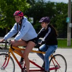 A youth participant and helper ride a tandem bike