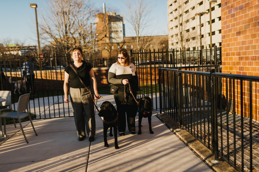 Chicago Lighthouse employees Maureen Reid (left) and Adnana Saric (right) walk outside with their dog guides.