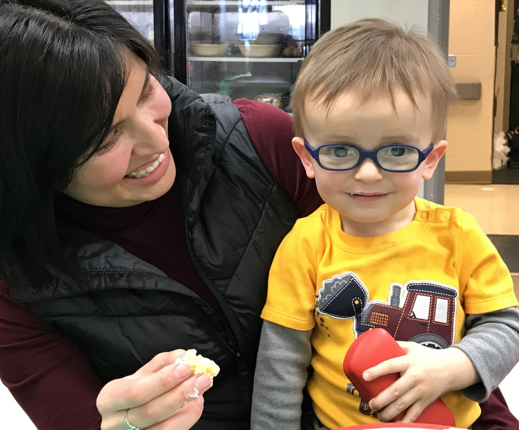 Young child who is visually impaired, wearing glasses, smiling as he sits on his mom's lap