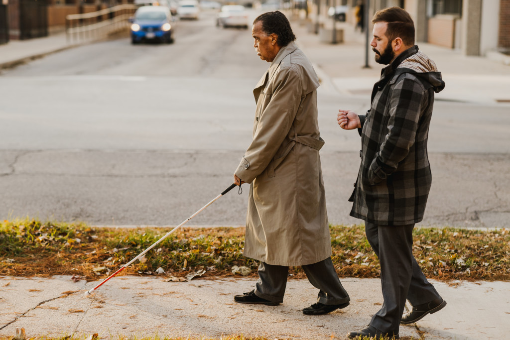 Orientation and Mobility Instructor Jaret Bozigian works with a client as they use their white cane while walking on the sidewalk