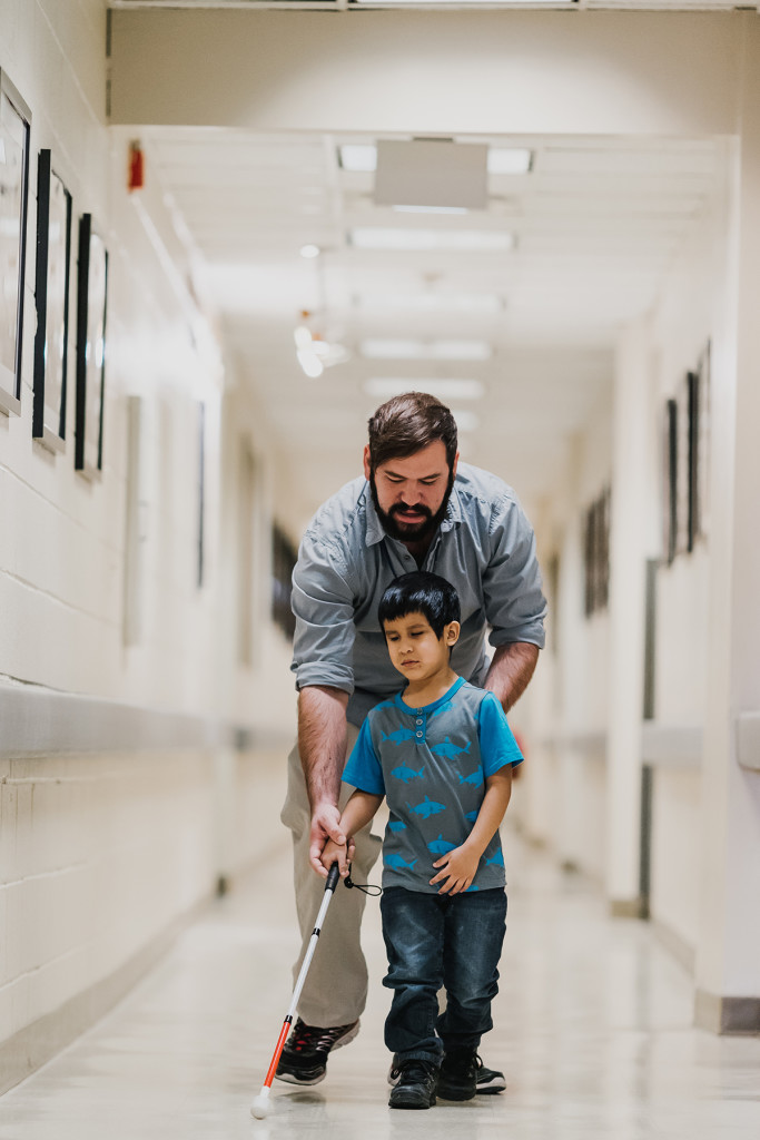 Orientation and Mobility Instructor Jaret Bozigian works with a young student who is using a white cane.