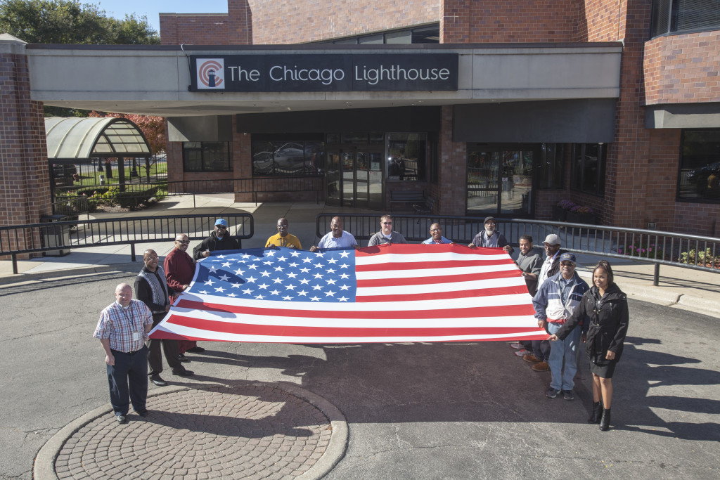 Veterans employed at The Chicago Lighthouse stand alongside the Flag of The United States.