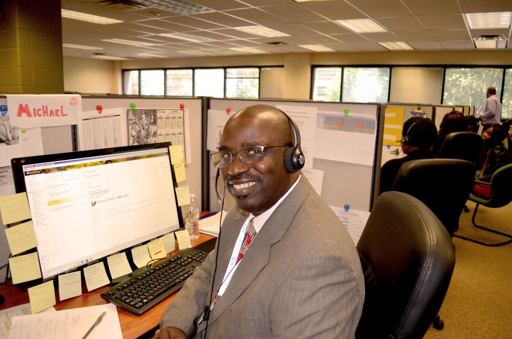 Michael Smith, an employee of our Illinois Joining Forces Call Center, smiles at his desk.
