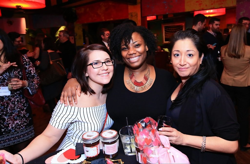 Three women smile standing behind a table with sweets.