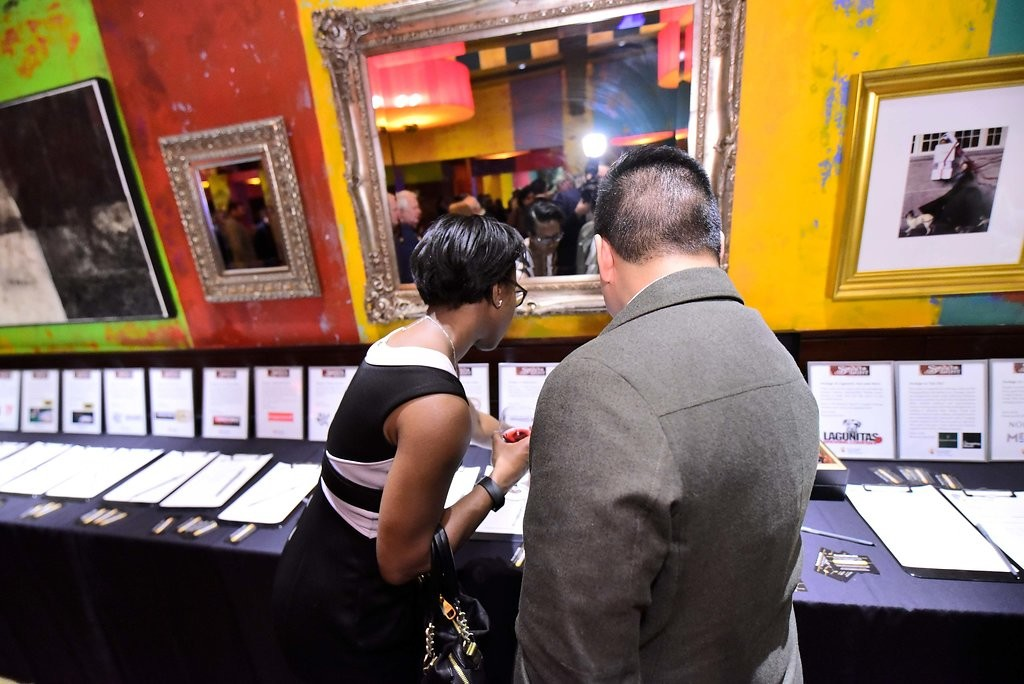 Two people browse silent auction bid sheets displayed on a table.