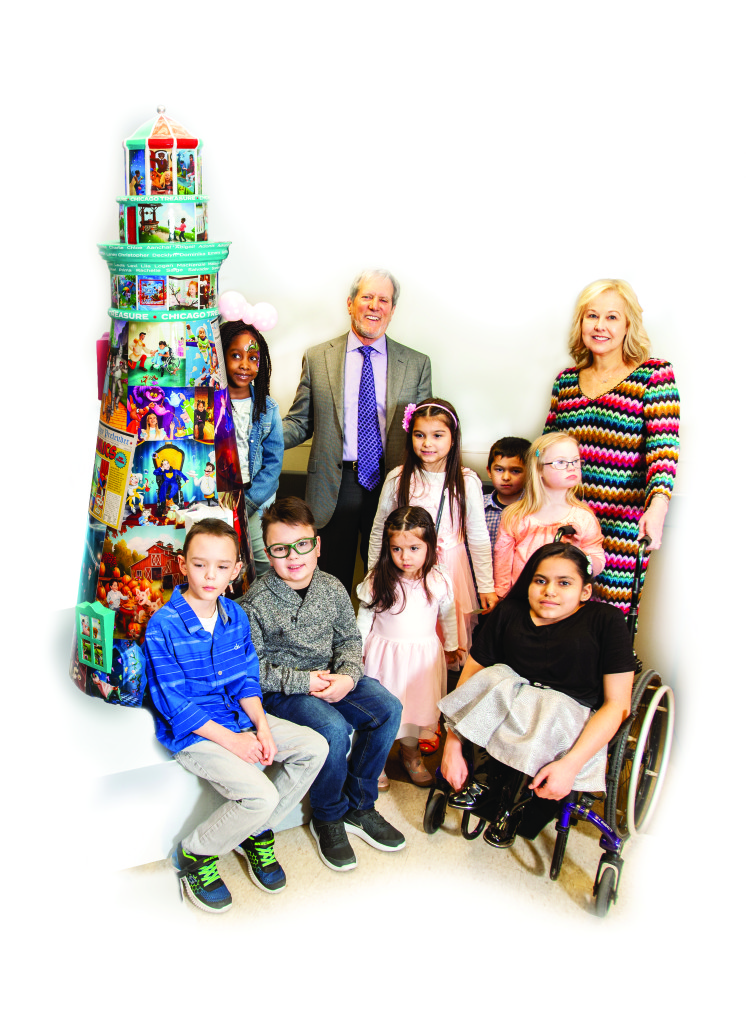 President/CEO Dr. Janet Szlyk and Chairman of the Board Gary Rich pose in front of a painted Lighthouse sculpture with several young children, many who are disabled