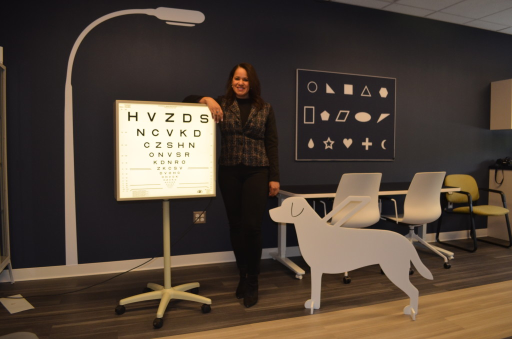 A female researcher stands in the Hilton Center for Prosthetic Vision Rehabilitation. In the room are high contrast graphics for testing