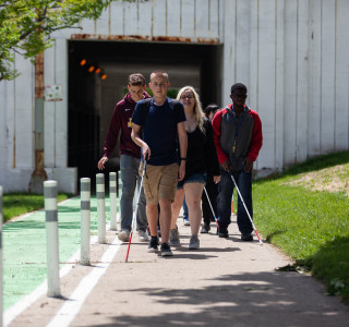 A group of teens who are visually impaired or blind along with their counselors walk on the sidewalks of downtown Chicago