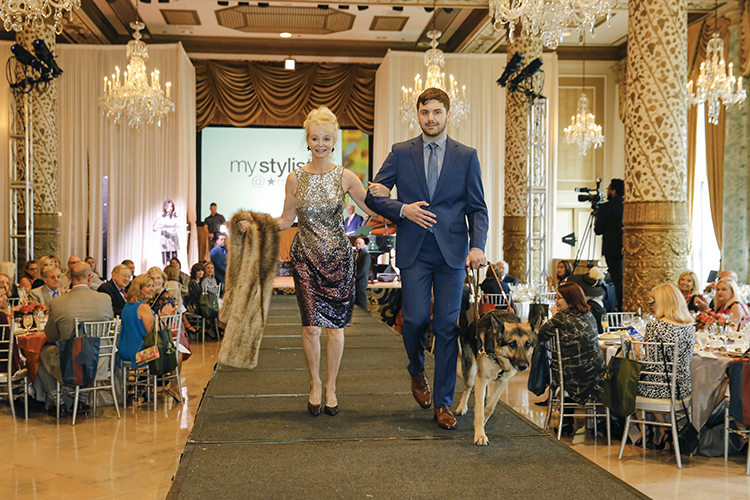 Ben walks down a fashion runway with his guide dog and a model at The Lighthouses' FLAIR fashion show