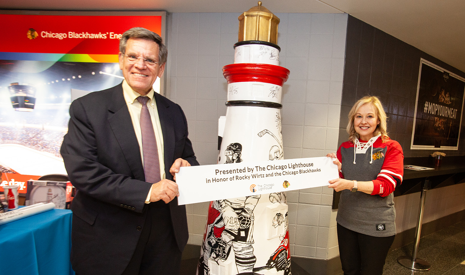 Chicago Blackhawks Owner Rocky Wirtz is presented with the Lighthouse on The Mag Mile sculpture: One Goal, by Lighthouse President/CEO Dr. Janet Szlyk.