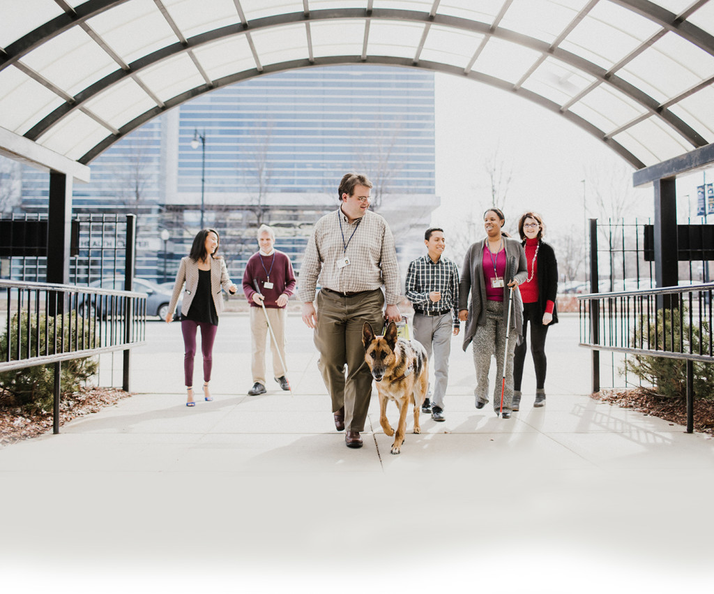 A group of six Chicago Lighthouse employees walk under the glass archway to the building. Two of the employees utilize a white cane and one has a German Shepherd guide dog.