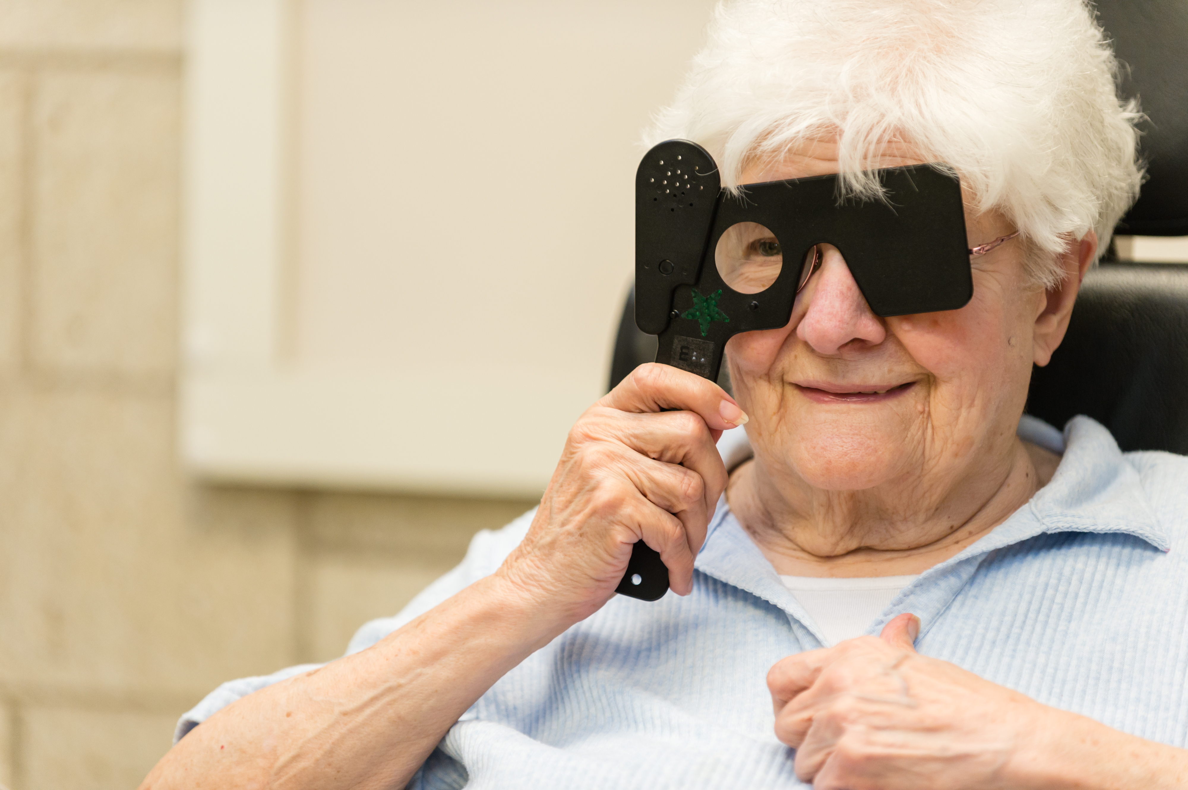 Patient in a low vision eye exam holding a tool in front of her eye