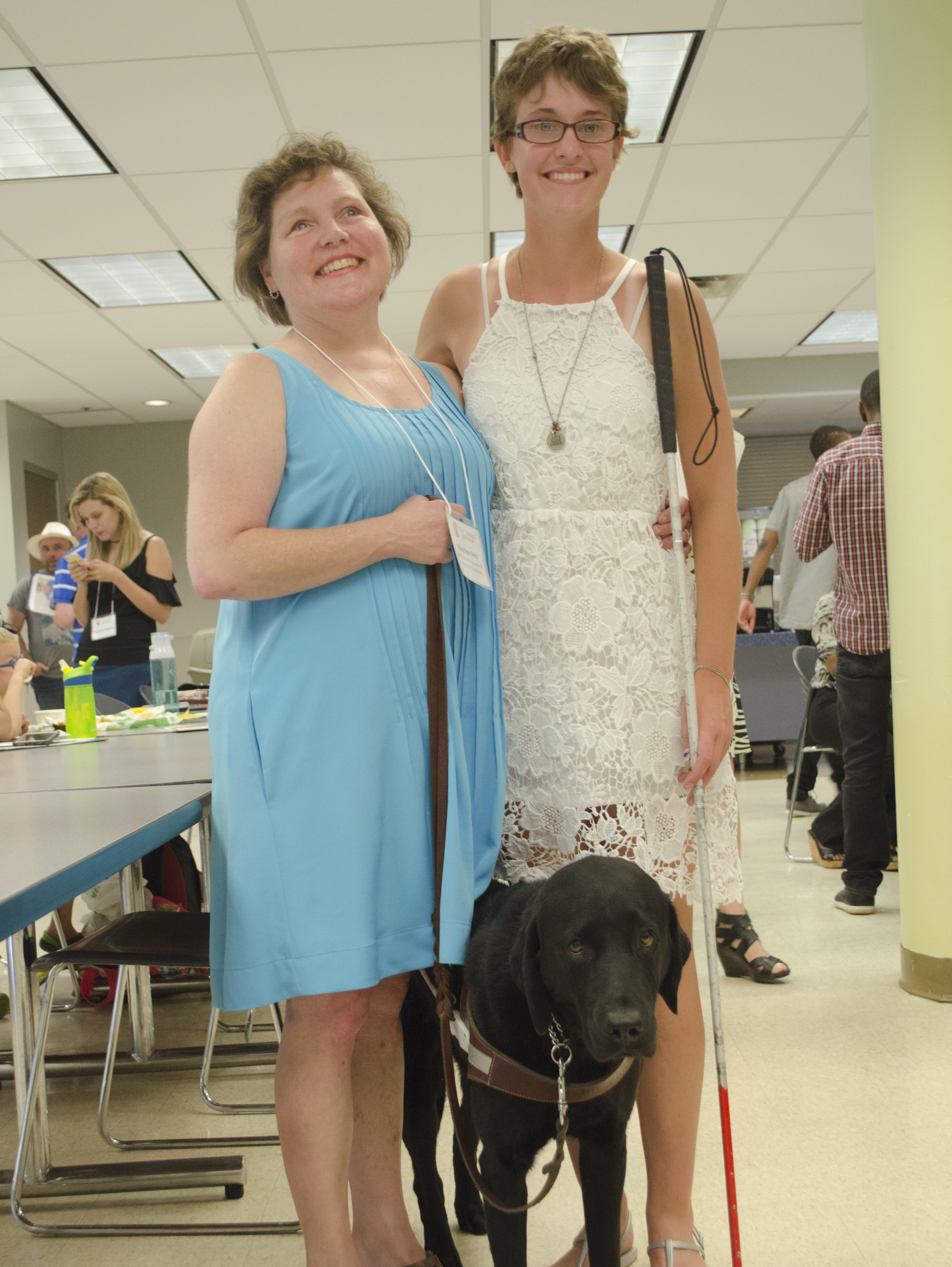 Scholarship Coordinator Maureen Reid and her guide dog Gaston smile alongside a scholar during our annual Scholarship Ceremony.