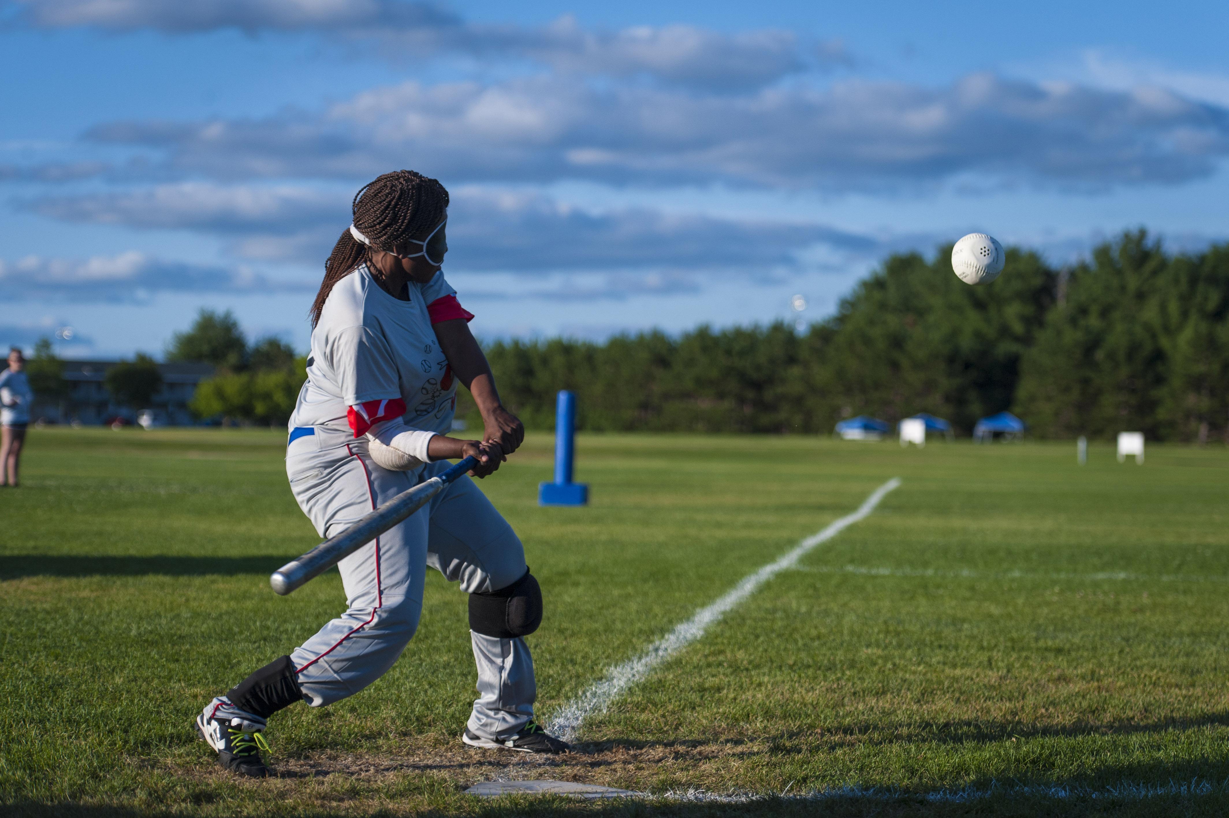 Image of Kalari swinging the bat during a beep baseball game