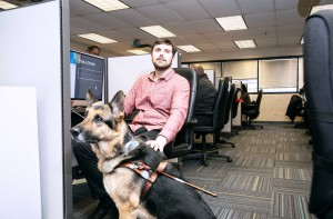 Call Center employee with guide dog sitting next to