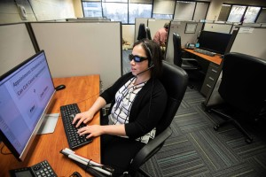 call center employee, who is blind, sitting at a desk in front of a computer.