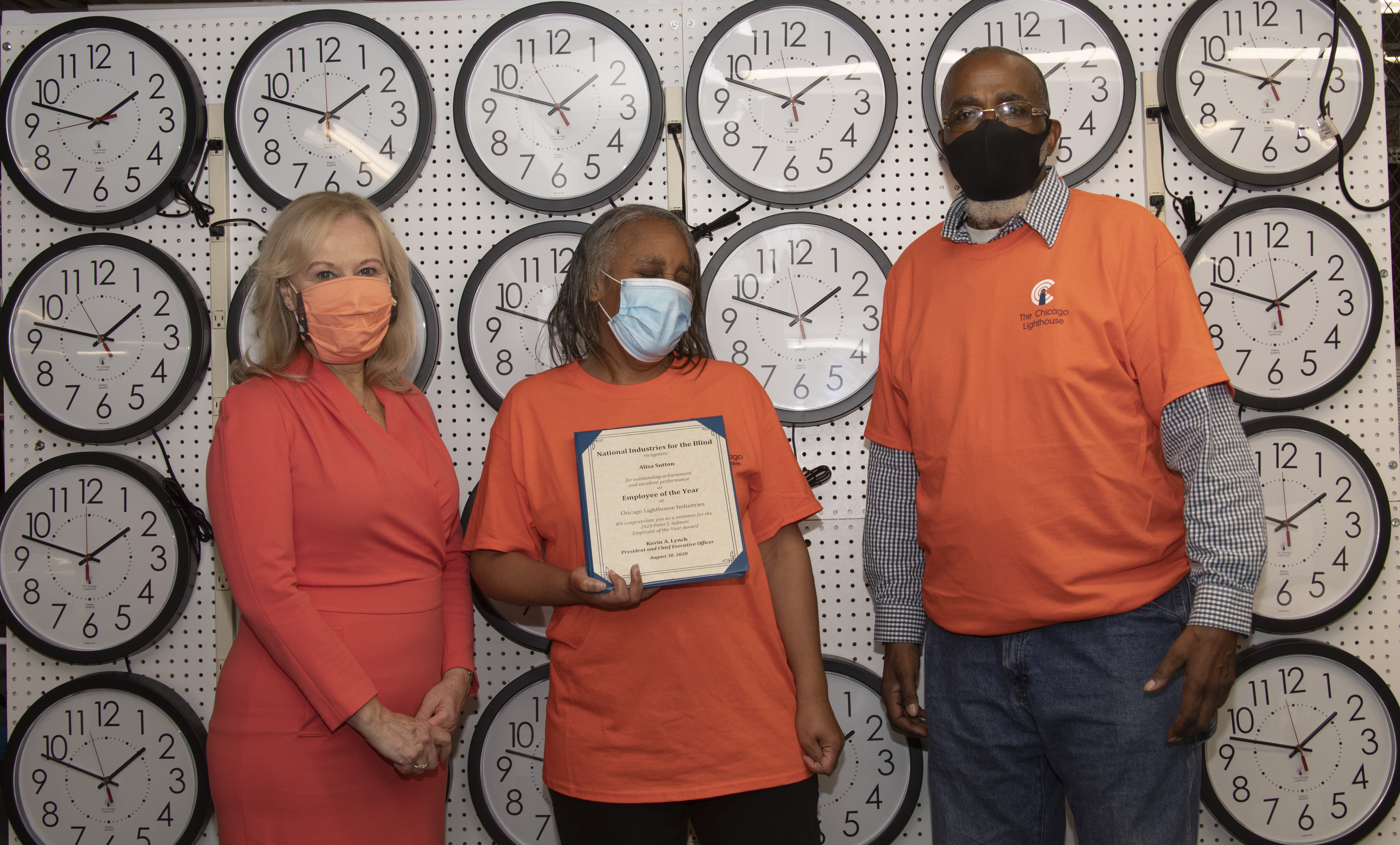 Dr. Janet Szlyk presents a certificate to Alisa Sutton who works as a clock assembler for Chicago Lighthouse Industries. Behind them is a testing wall of clocks.