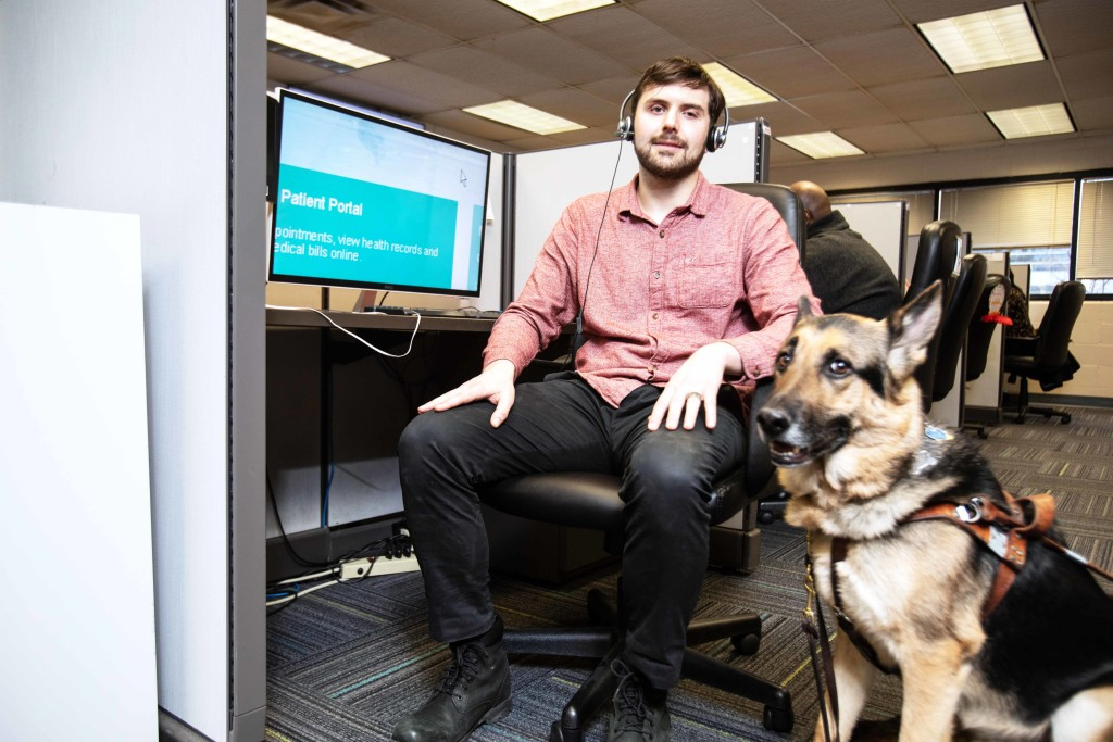 A call center agent is seated at his desk with his guide dog.
