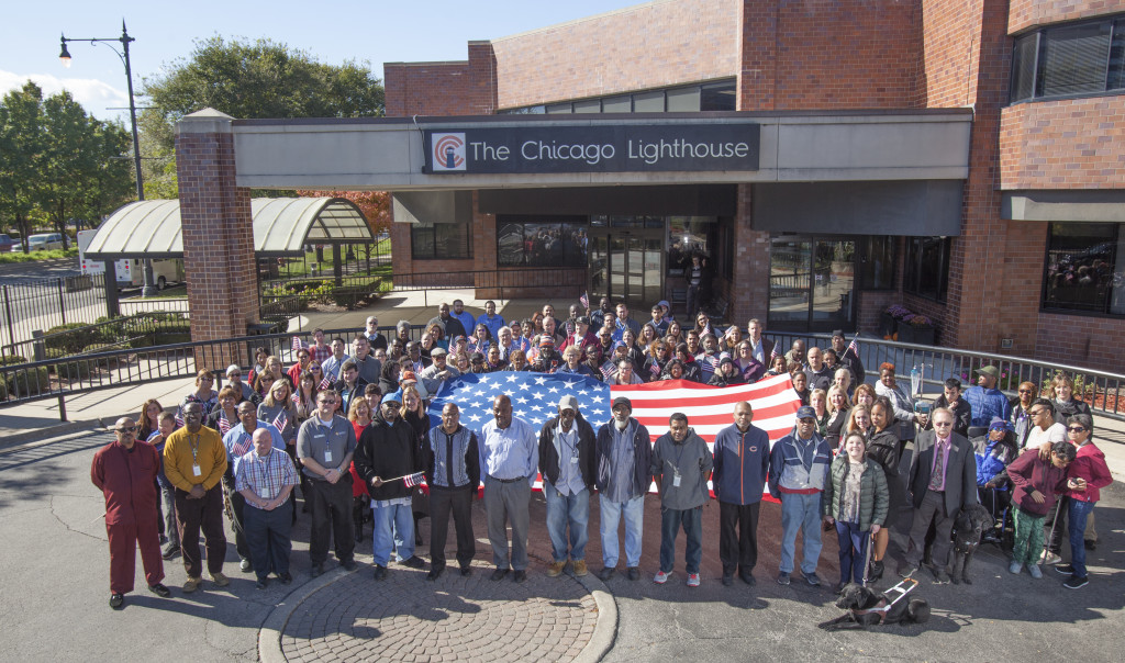 A large group of people (approximately 50) gather around a large USA flag outside of the Chicago Lighthouse. In the front row are employees of the Lighthouse who are Veterans