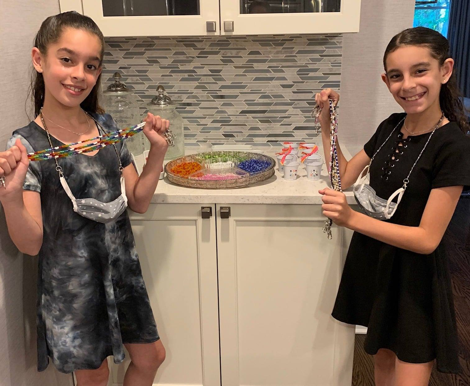 Twin sisters hold their beaded mask holders and smile