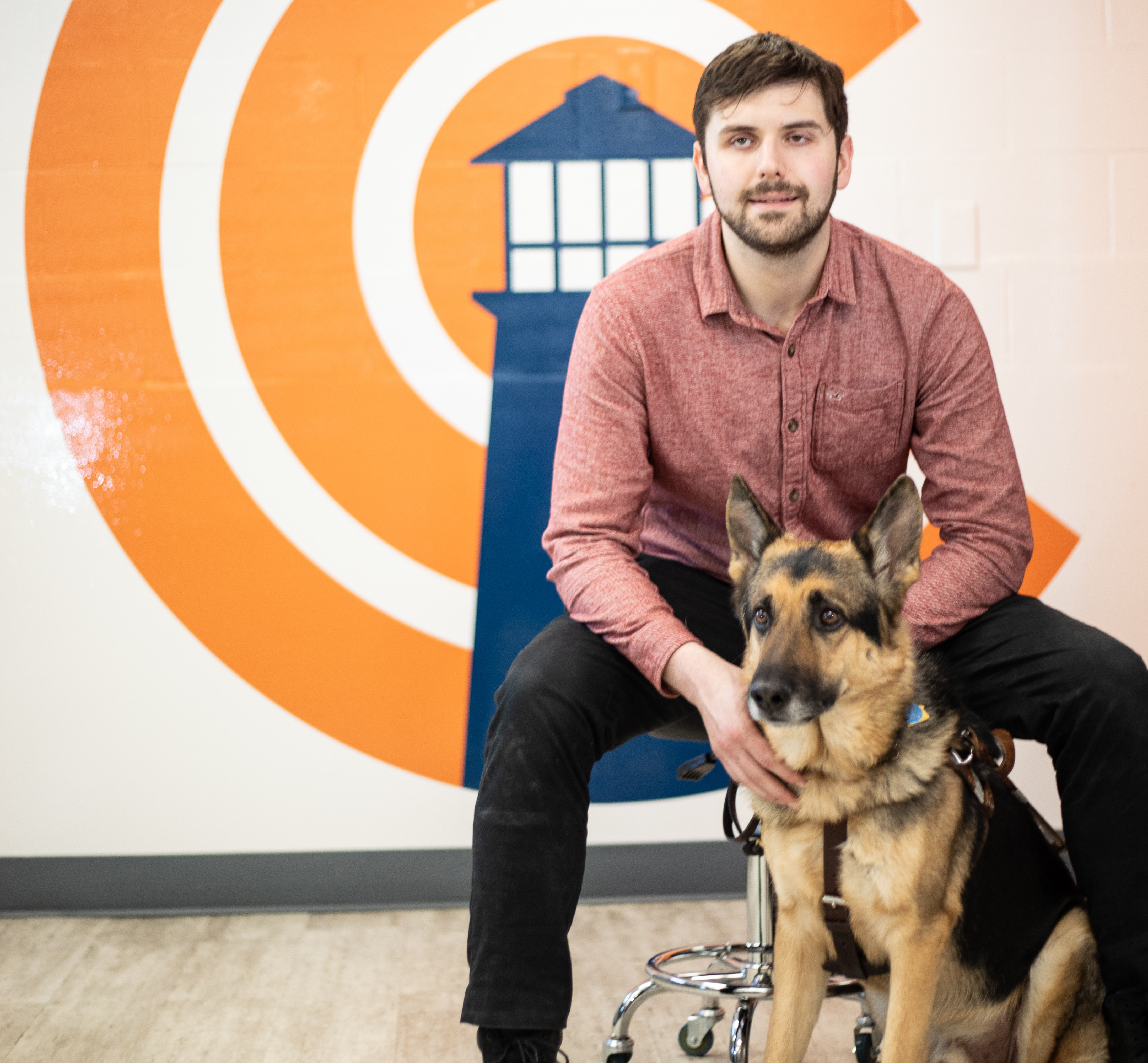 Ben and his guide dog, sammie, sitting in front of a wall with the chicago lighthouse logo