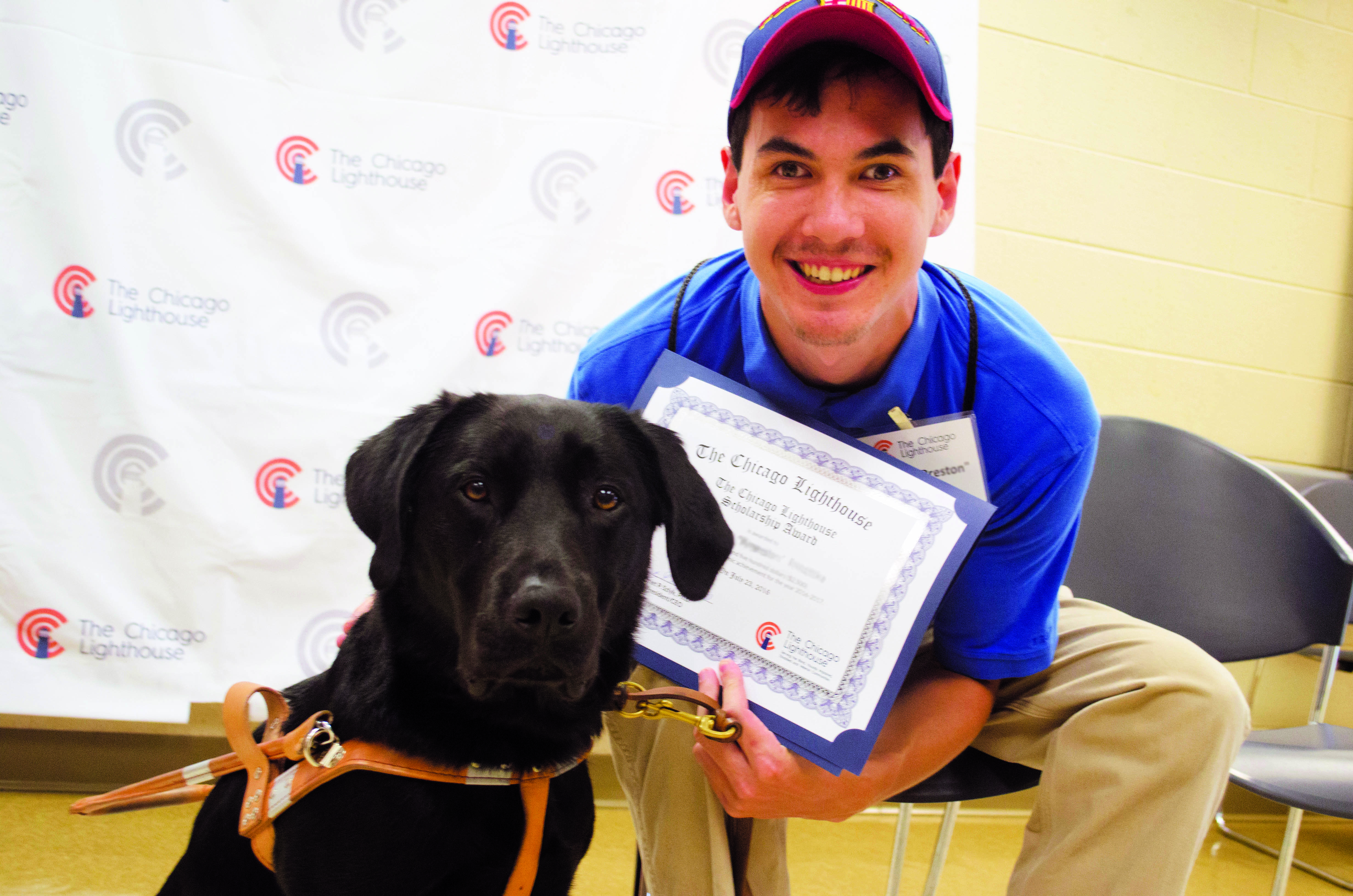 a past scholarship recipient sitting and smiling holding his award, next to his guide dog