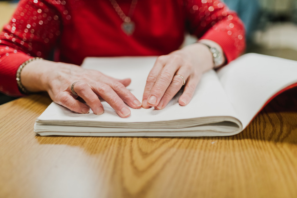 close up view of hands reading braille in a book