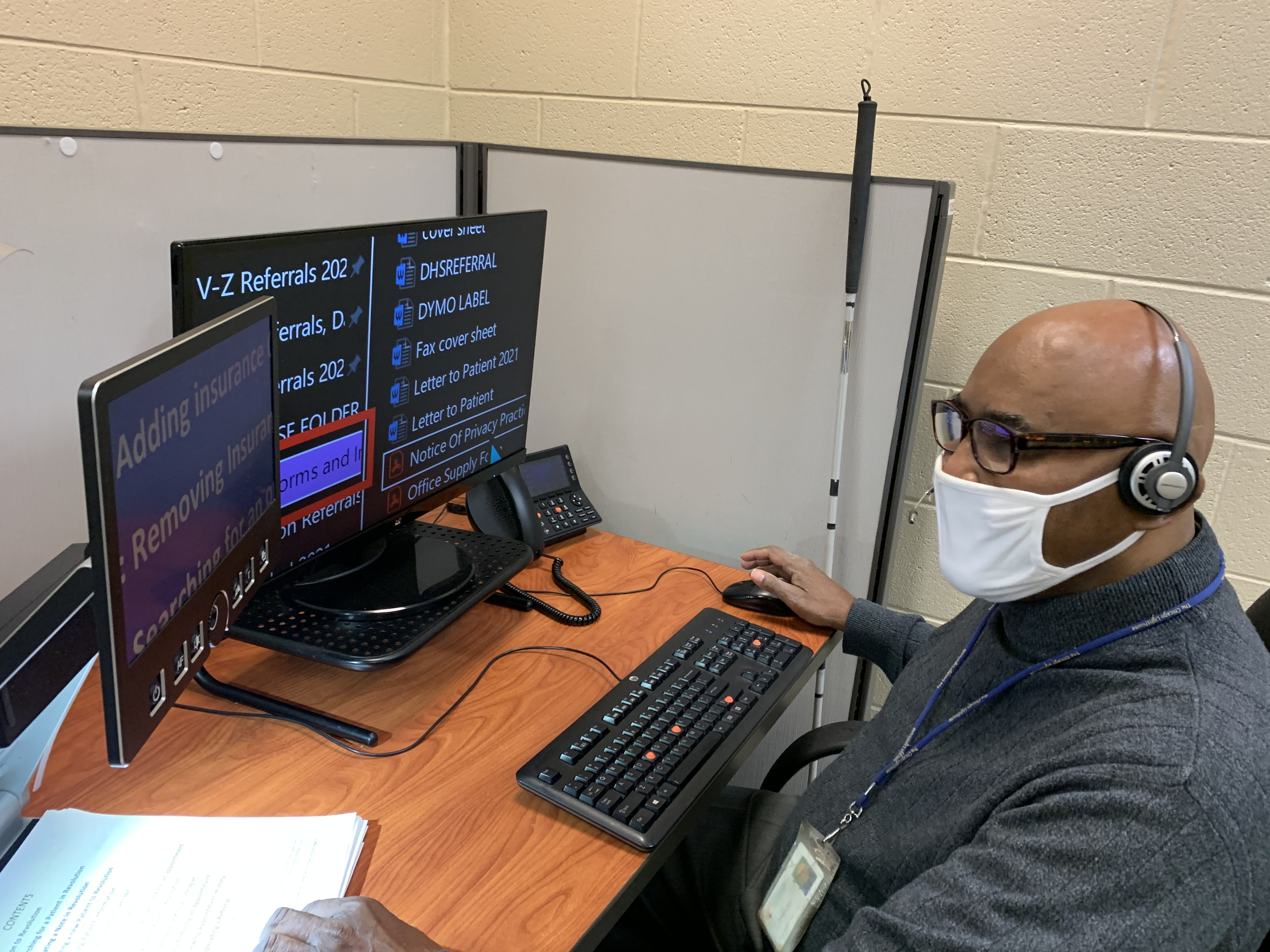 Joseph sitting at a desk in front of his computer, wearing a mask and glasses, with his cane leaning on the desk next to him
