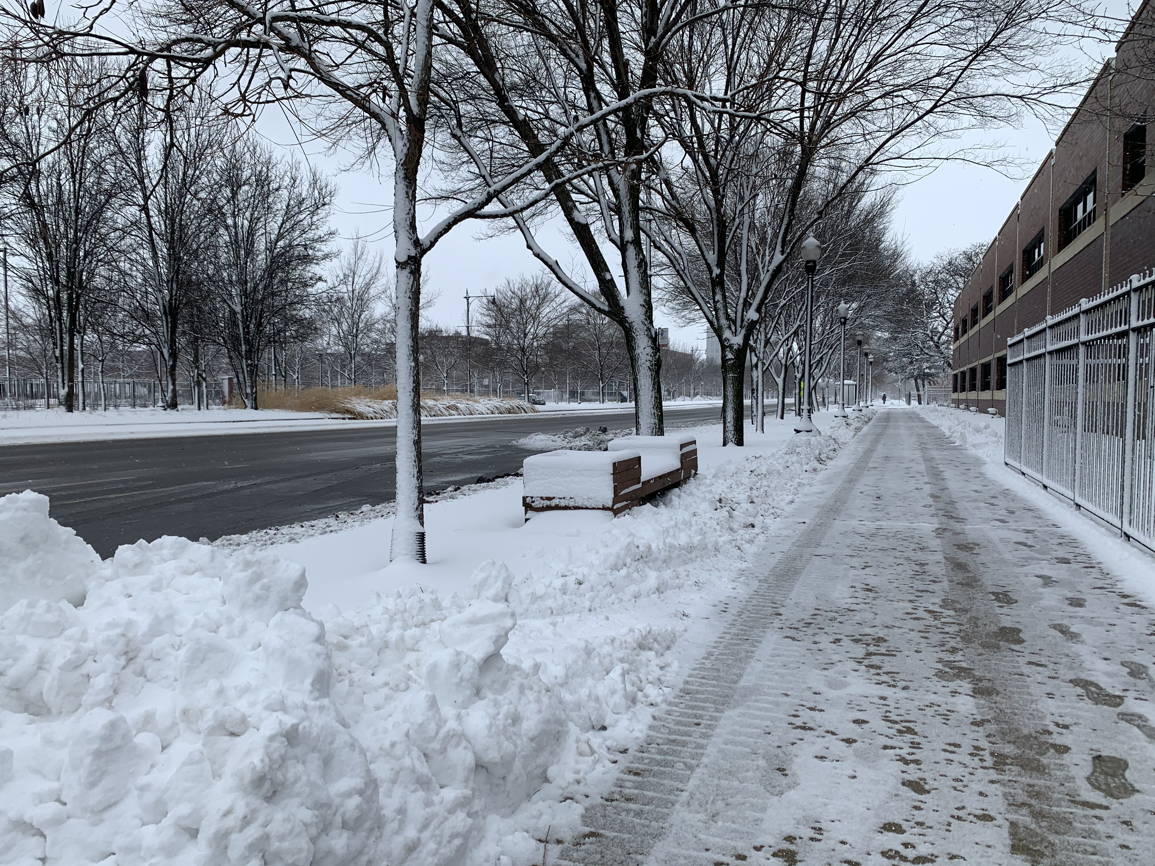 A snow street and sidewalk that has been shoveled off.