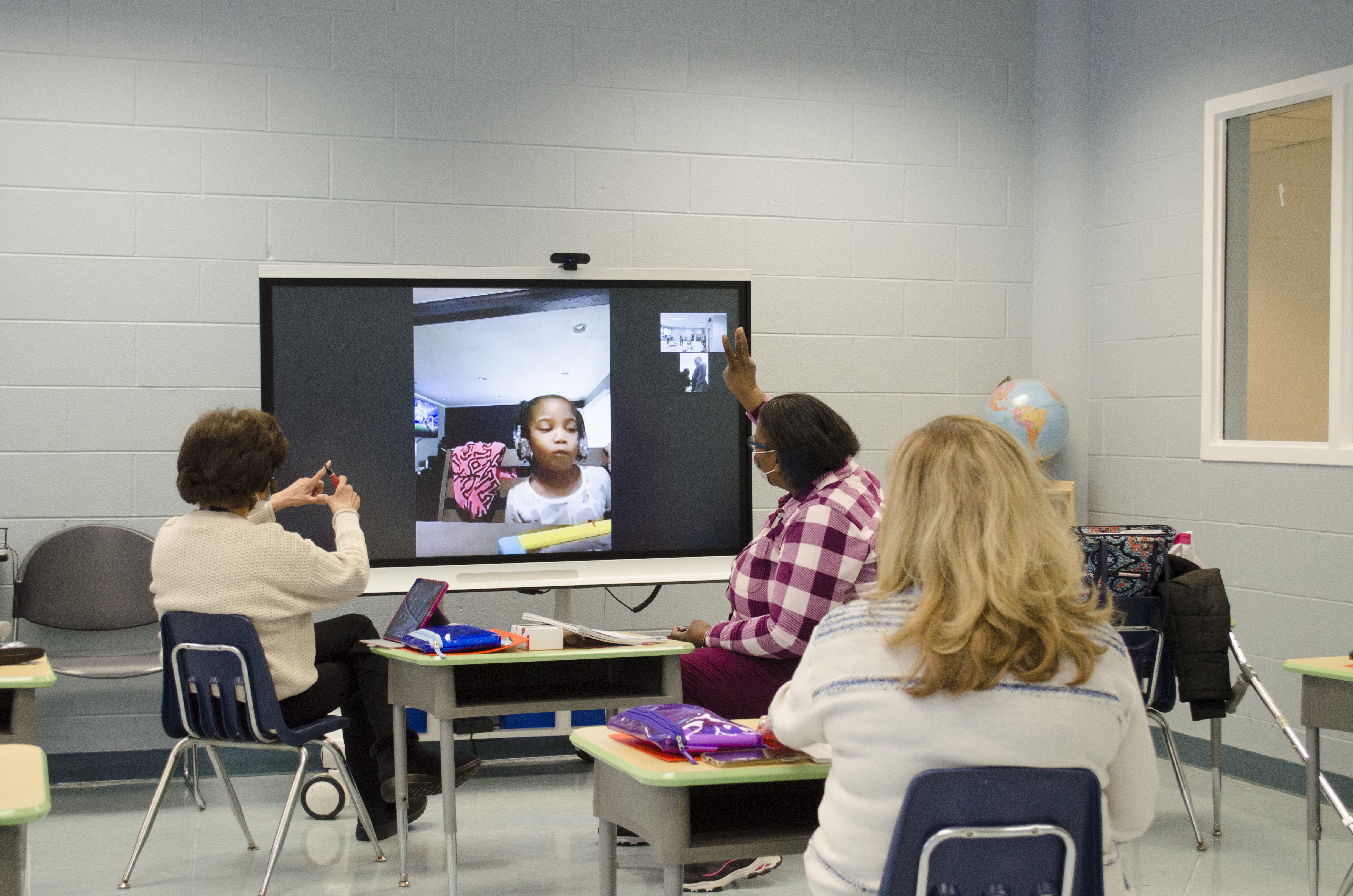 The Lighthouses' preschool teachers conducting e-learning over zoom, and sit in front of a large screen, talking with their students