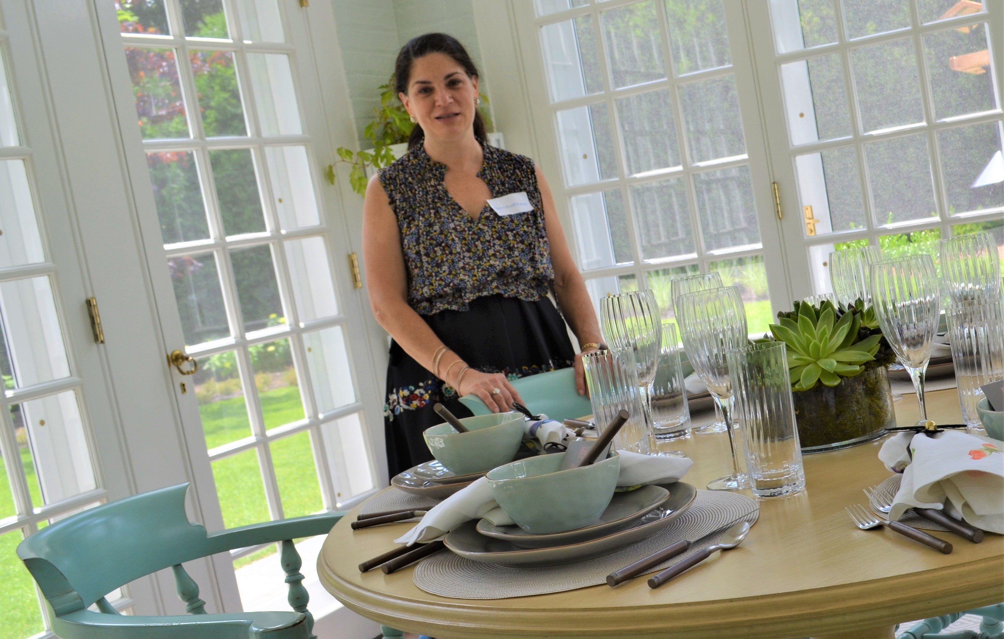 Ceryl Kraff-Cooper smiling and standing behind a table at the chicago lighthouse's house and garden walk