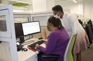 A woman who is blind uses accessible software by Epic to schedule patient appointments in a call center. Her supervisor consults with her.