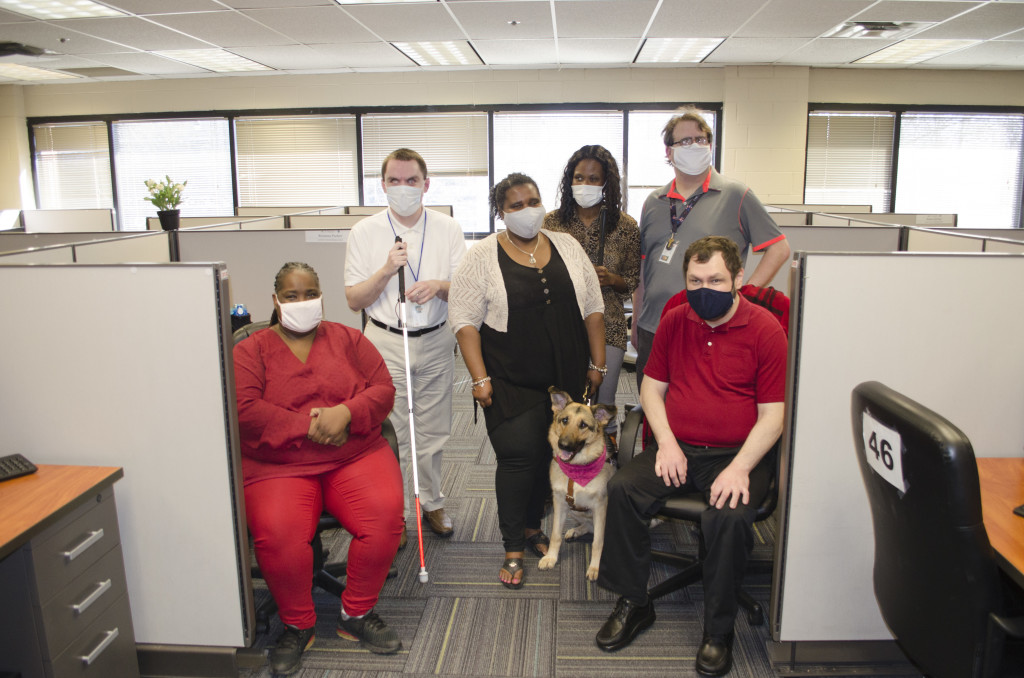A team of 6 individuals all whom are blind, pose in the call center where they work. A guide dog is present.
