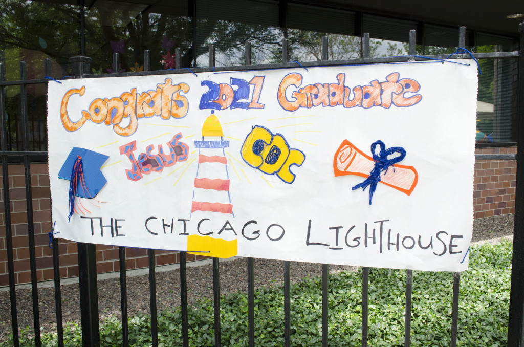 A tactile paper banner is displayed across the fencing of The Lighthouse. Sign reads: Congrats 2021 Graduate Jesus, The Chicago Lighthouse